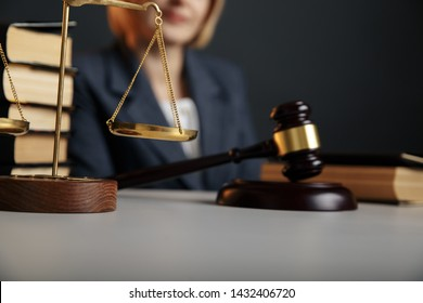 Female jurist isolated at the dark background. Books and gavel with justice scales.