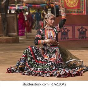 Female kalbelia dancer in traditional tribal dress performing at the annual Sarujkund Fair near Delhi, India