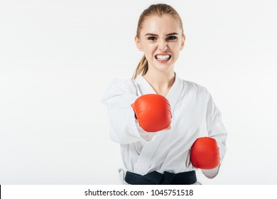 female karate fighter exercising with gloves and mouthguard isolated on white