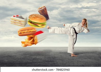 Female karate kicks fast food. The concept of healthy eating.