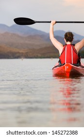 Female Kayaker with Arms and Paddle Raised Above Head