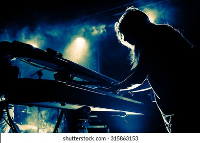 Female keyboards player on stage during concert, backlight, colors intentionally altered