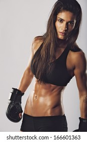 Female kickboxing fighter with an intense look. Muscular woman with boxing gloves looking at camera against grey background