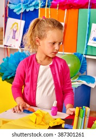Female kid holding colored paper on table in kindergarten. Children's Art Class.