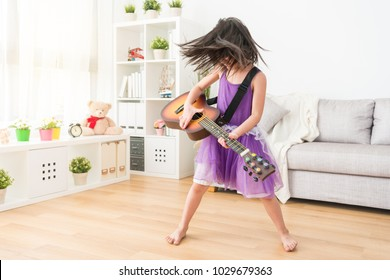 The female kid playing in the living room imagine herself a super rock star. Shaking her head so hard and enjoying the background music.