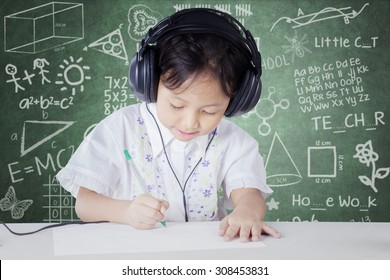 Female kindergarten school student studying in the classroom while wearing headphones and write on the paper