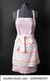 Female kitchen apron on a mannequin on a black background