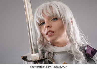 Female Knight In Shining Armour with sword isolated on the gray background