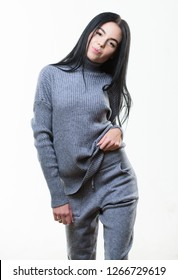 Female knitwear. Fashionable knitwear. Knitwear concept. Feel warm and comfortable. Woman wear grey textile suit blouse and pants. Warm comfortable clothes. Casual style fashion for every day.