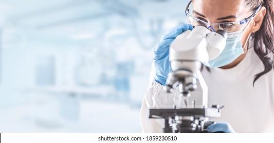 Labortechnikerin in Schutzbrillen, Handschuhen und Gesichtsmasken neben einem Mikroskop im Labor.
