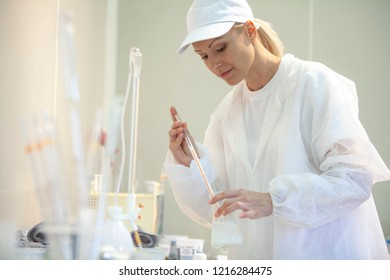 Female lab worker doing tests in a laboratory in an industrial cheese production factory