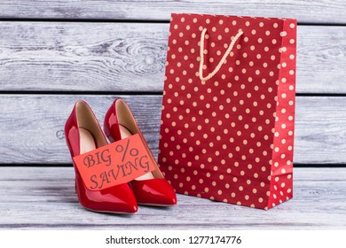 Female lacquered shoes and shopping bag. Red paper bags, leather stilettos and card with inscription big saving.