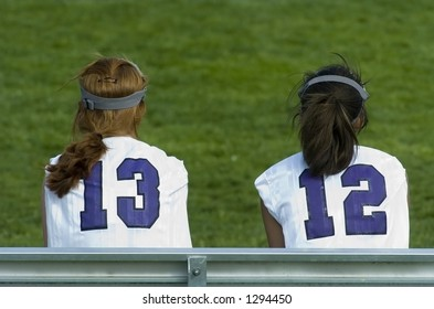 Female lacrosse players wait to enter the game