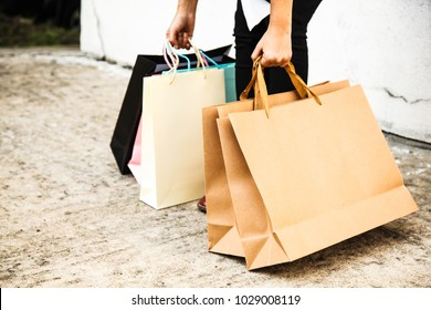 Female Lady lifting Colorful Shopping Bags Concept from ground on white wall background. Wrong posture, back bending, bad ergonomics, Health care, Back Pain, Injury Prevention and Awareness concept.