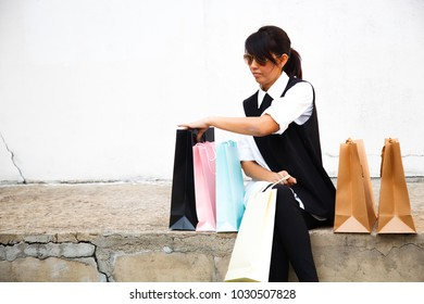 Female Lady Shopping Concept with copy space background. Asian Buddy Female Shoppers happy shopping, sitting next to colorful shopping bags