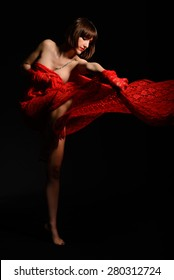 Female latin dancer semi covered with red fabric