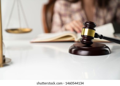 Female lawyer, bokeh background, gavel, hourglass, scales, statue of justice.