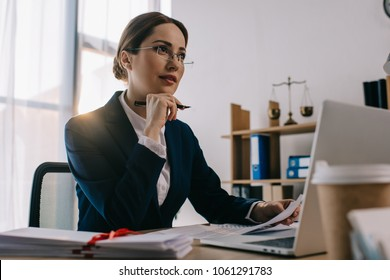 female lawyer in eyeglasses at workplace with documents and laptop in office