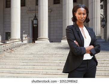 A female lawyer (or business person) stands in front of a courthouse or municipal building with her arms folded.
