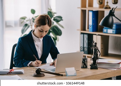 female lawyer in suit at workplace with laptop, gavel and femida in office