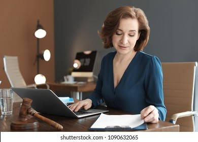 Female lawyer working with laptop at table in office