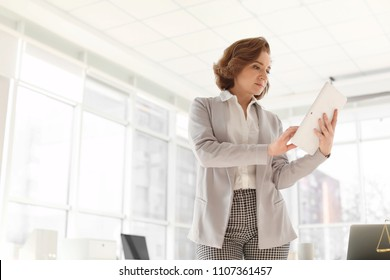 Female lawyer working with tablet in office