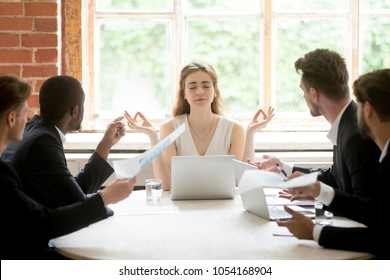 Female leader being calm meditating at work briefing not listening to male colleagues bullying and blaming. Businesswoman practicing yoga ignoring angry coworkers. No stress, positive state of mind