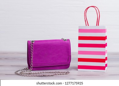 Female leather bag and shopping bag. Pink womens pouch and striped gift bag on wooden background. Shopping and purchases concept.