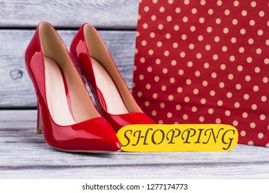Female leather heels on wooden background. Red lacquered stilettos, shopping bag and card with inscription shopping. Fashion and purchases concept.