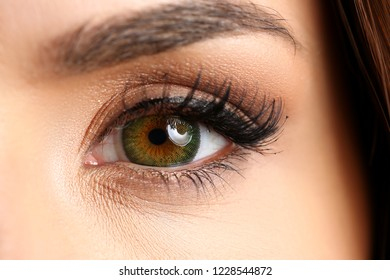 Female left emerald green coloured eye extreme closeup. Low light technique oculist and perfect vision contact lens shadow makeup cosmetics mascara concept