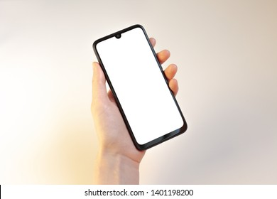 Female left hand holding phone on white background with clipping path around blank screen of smartphone