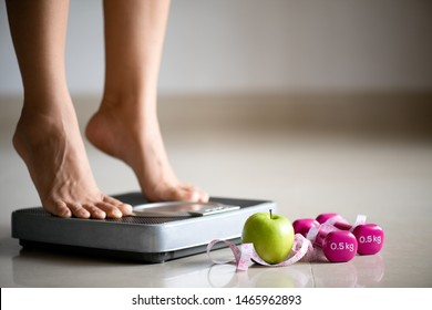 Female leg stepping on weigh scales with measuring tape, pink dumbbell and green apple. Healthy lifestyle, food and sport concept.