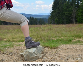 Female leg in tracking shoe resting on a stone in mountain