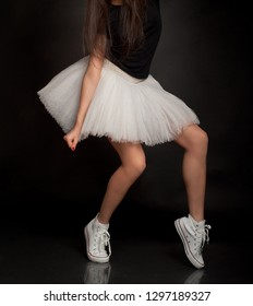 Female legs of ballet dancer with tutu and sneakers shoes in studio background