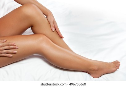 Female legs and beautiful glowing skin on white sheet