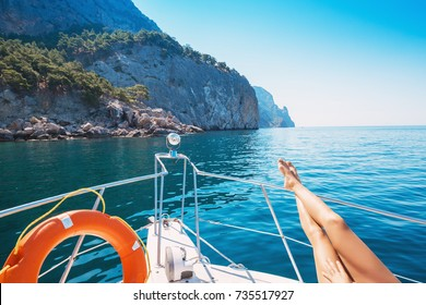 Female legs. A beautiful woman relaxes on a private yacht in the sea near the islands.