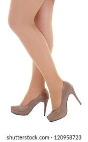 female legs in beige shoes isolated over white