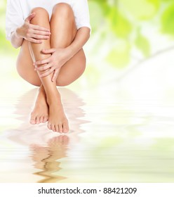 female legs being massaged under clean water waves over green spring background - spa and healthcare concept