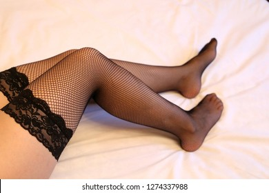 Female legs in black fishnet stockings, sexy girl lying on bed. Black lingerie, naked body, fashion underwear, woman before sex in bedroom