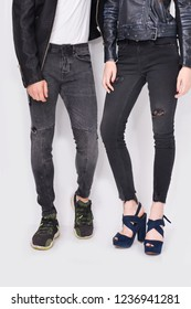 female legs in black jeans with punk leather Jacket and high hell shoes and male in blue jeans with  shoes, in studio