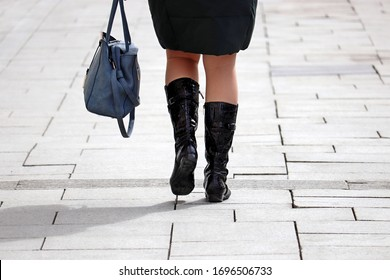 Female legs in black leather boots. Woman with handbag walking on the city street in early spring
