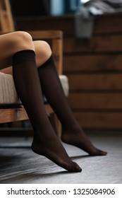 Female legs in black nylon knee socks