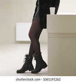 Female legs in black tights, fur coat and boots in profile