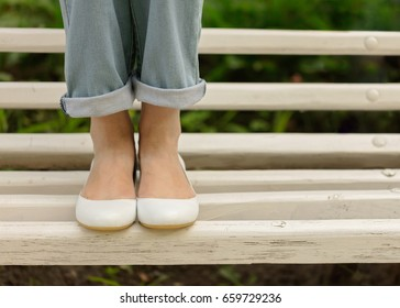 Female legs in blue jeans and white shoes on a white bench. Selective focus.