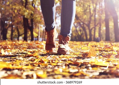 Female legs in boots on autumn leaves