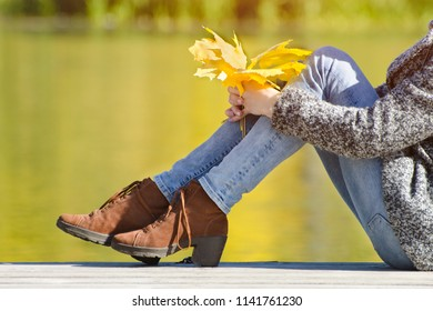 Female legs in brown shoes against the background of a river. Autumn day