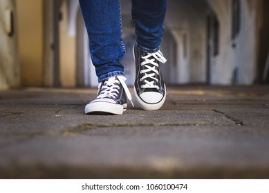 Female legs in canvas shoes walk along the cobbled street. Fashionable woman wearing sneakers walking in old town