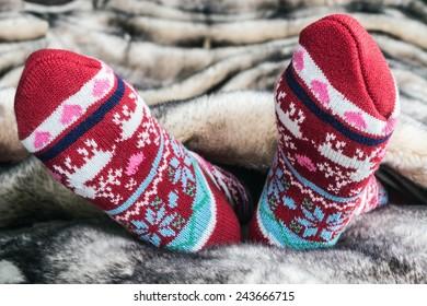 Female legs in Christmas socks under a blanket of fur