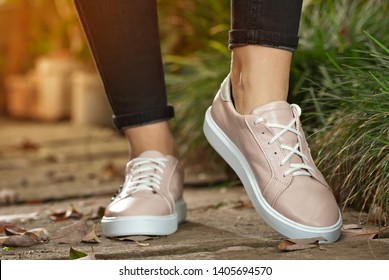 Female legs close-up. Sports sneakers on asphalt against green plants. Shoes in a tropical climate arranger.