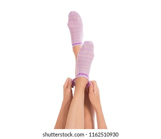 Female legs in color socks. Female hands putting on a sock, french manicure. Close up, isolated on white background.